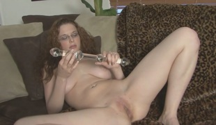 Busty redhead with glasses masturbating on a daybed