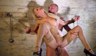 Blond with large tits is sitting down on a large erection