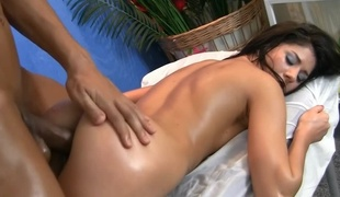 A dark haired woman is getting a dick in her during a massage